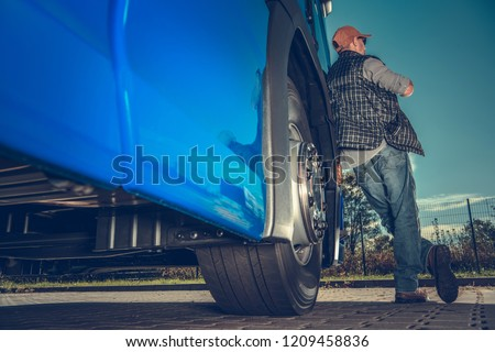Freight Industry Driver. Caucasian Trucker and His Semi Truck in the Rest Area.