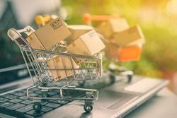 Freight or shipping service for online shopping or ecommerce concept : Paper boxes or cartons in metal shopping cart on a computer laptop keyboard. Customer always buy things via internet worldwide.