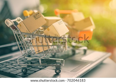 Freight or shipping service for online shopping or ecommerce concept : Paper boxes or cartons in metal shopping cart on a computer laptop keyboard. Customer always buy things via internet worldwide. #702046183