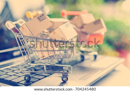 Freight or shipping service for online shopping or ecommerce concept : Paper boxes or cartons in metal shopping cart on a computer laptop keyboard. Customer always buy things via internet worldwide. #704245480