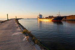 Freight ship is moving along heap of wood and breakwater in harbor channel of Liepaja, Latvia at sunset with clear sky in background.