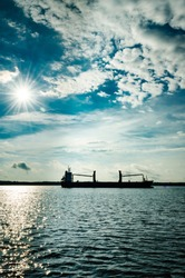 Freight Ship silhouetted with a satburst sun behind it against a cludy blue sky and dark blue water