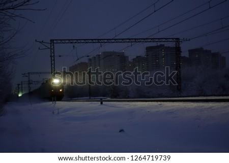 Freight train at night. The headlights and locomotive headlights illuminate the falling snow. Russia. #1264719739
