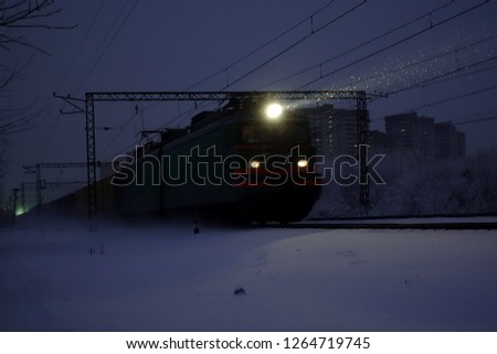 Freight train at night. The headlights and locomotive headlights illuminate the falling snow. Russia. #1264719745