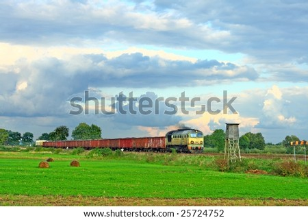 Freight train hauled by the diesel locomotive is passing the countryside