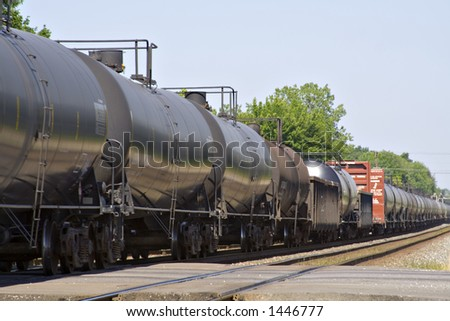 Freight train of many tank cars on tracks speeding through a small town.