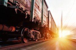 Freight train passing at sunset. Train carrying cargo under the rays of the setting sun.