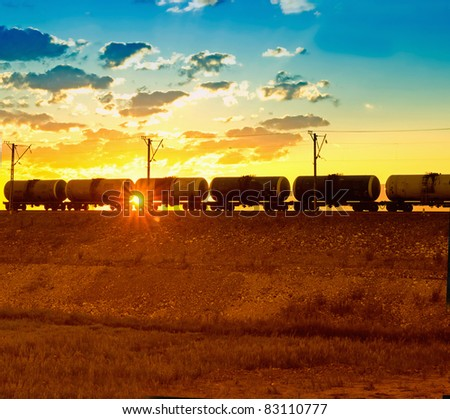 Freight train passing by on sunset beam