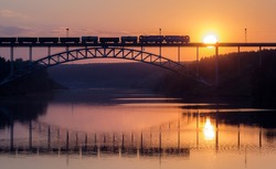 freight train rides on the railway bridge over the river during sunset, a summer evening the river Iset