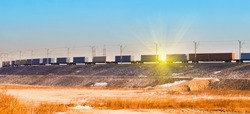 Freight train with cargo containers at sunset
