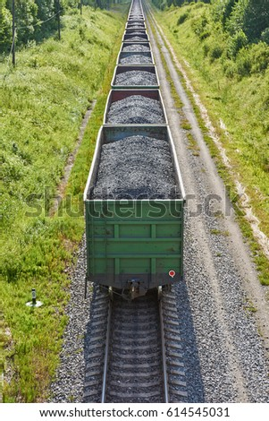 Freight train with coal passing the forest