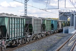 Freight train with covered hoppers passes the bridge. Hopper - self-clearing enclosed railroad freight car for dry and bulk loads. Rail freight