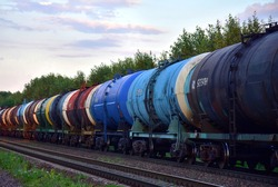 Freight train with petroleum tank cars on railroad. Rail cars carry oil and ethanol. Railway logistics explosive cargo. Transportation of methanol, crude and gas. Petrochemical tank cars