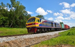 Freight trains on railway tracks curve in countryside with blue sky background