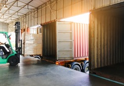freight transportation, cargo courier shipment. forklift driver unloading cargo pallets into a truck container.