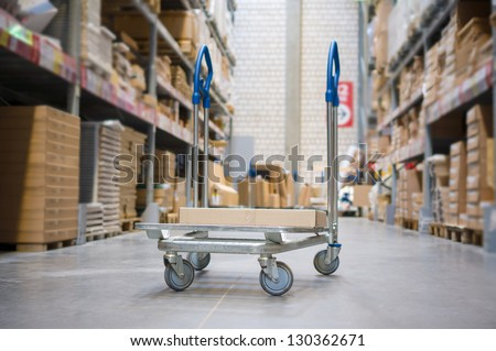 Freight trolley with box on it on modern warehouse