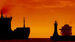 FREIGHTER AND CRUISER SHIP - Ships on water route at sunrise on the roadstead of port in Gdynia