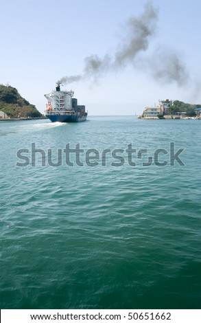 Freighter navigate on ocean with blue sky and green water in Kaohsiung, Taiwan.