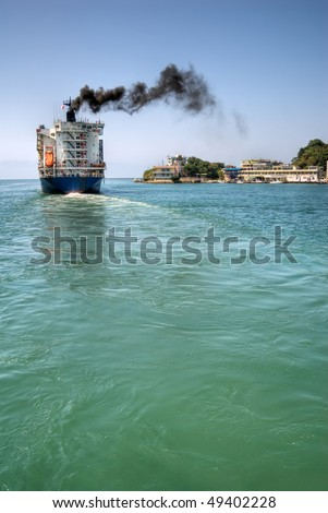 Freighter navigate the port with black smoke of sea in Kaohsiung, Taiwan.