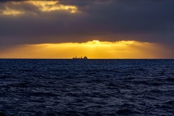Freighter ship in the distance above the sea horizon on a sunset with dramatic sky. Gran Canaria. Spain