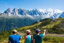 French  Alps summer travel. Three friends (unidentified people, back view) admiring beautiful snow covered Mont Blanc mountains range.  France nature hiking tourism background. Active vacation concept