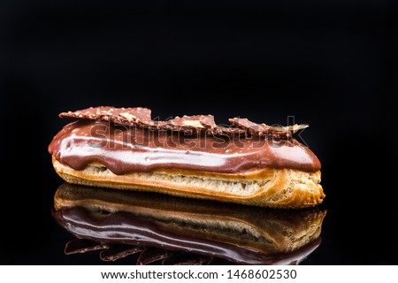 French Artisan Eclair on Black Reflective Background,Copy Space. Patisserie Bakery Product.