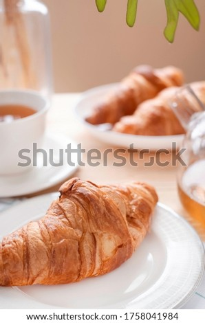 French baked croissants sprinkled with icing or powered sugar on wooded table background. Eating croissant with tea in café is healthy. Croissant is pastry served in café. Healthy lifestyle concept.