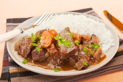 French beef stew in red wine, on a plate with rice. Known as daube de boeuf Provencal.