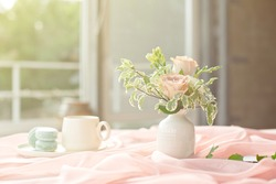 French blue macaroon plate and coffee cup standing on a wooden table with a pink tablecloth white vase with flowers roses and greens.