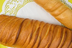 French bread - baguette and loaf. White lace doily, bright yellow background.