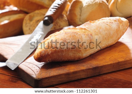 French bread baguette on vintage wooden bread board and knife. Selective focus with background of assorted bread rolls.