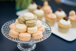 French cakes macaron or macaroon. Lightbrown macarons on a glass plate,