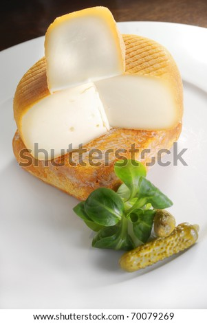 French cheese - Port salut and mariolles with cornichon on a white plate