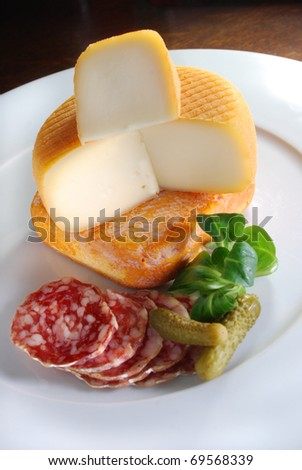 French cheeses on a plate surrounded by sliced salami, cornichon and lambs lettuce.