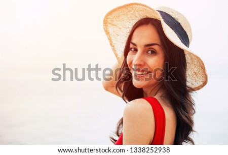 French chic. Girl in red swimsuit and camel hat, with a black line on it , is smiling right into the photographer's camera standing near the skyline which die away with the sea water.