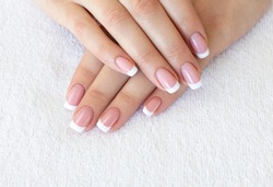 French classic manicure. Female fingers with beautiful nails on white terry towel, close up, selective focus. Spa, skin care, beauty treatment, salon and pretty woman concept