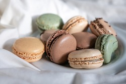 French Colorful Macarons Colorful Pastel Macarons on White Background green beige and Brown Macaron on plate dessert Sweet and colourful french macaroons pastry