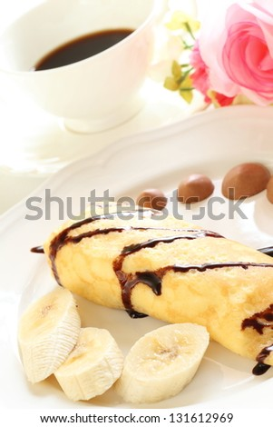 french confectionery, banana and chocolate crepe for gourmet dessert image with black coffee on background - stock photo