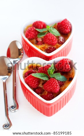 French creme brulee dessert with raspberries and mint covered with caramelized sugar in red heart shaped ramekins on white background