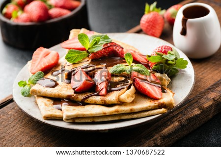French crepes with strawberries and chocolate sauce on a plate served on wooden cutting board. Closeup view. Tasty sweet breakfast, lunch or dessert Foto stock ©