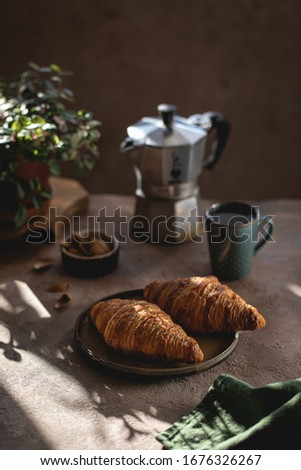 French croissant in the glare of the sun, croissants in a good light design, warm colors, homemade croissants with coffee, breakfast in the morning with croissants