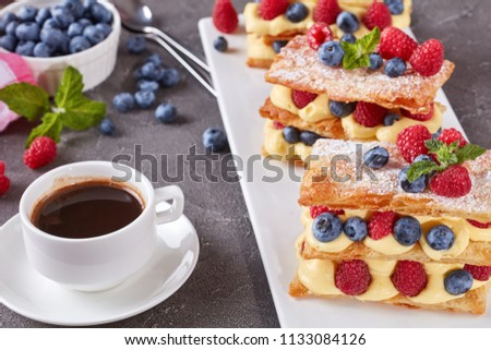 french dessert millefeuille of puff pastry and custard cream, raspberries, blueberries on a plate with cup of coffee and berries on a table, view from above, close-up