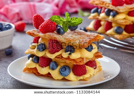 french dessert millefeuille of three pieces of puff pastry layered with custard cream, raspberries, blueberries on a white plate on a concrete table, view from above, close-up, macro