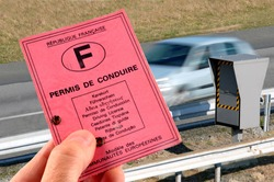 French driver's license in hand in close-up with speed control radar in the background