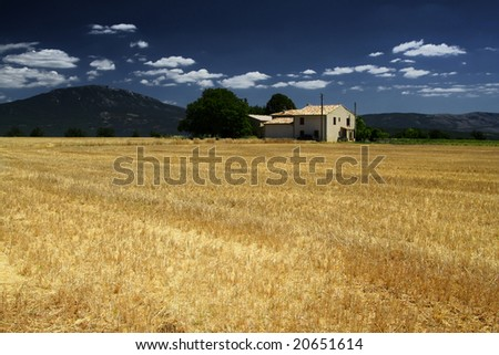 French farm house in a cut corn field.