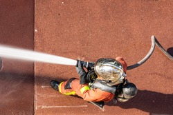 French firefighter with fire hose shot with top-down view