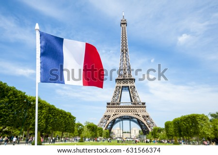 French flag flying in bright blue spring sky in front of the Eiffel Tower in Paris, France