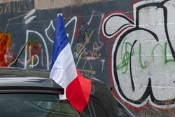 French flag on a car in front of a wall full of graffiti