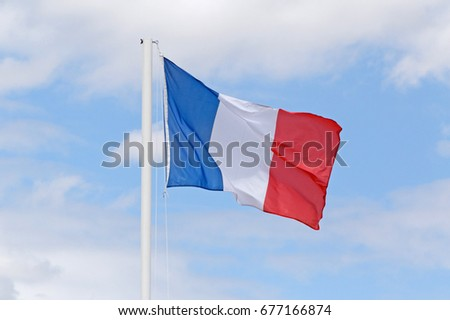 French flag on flagpole against blue sky with white clouds