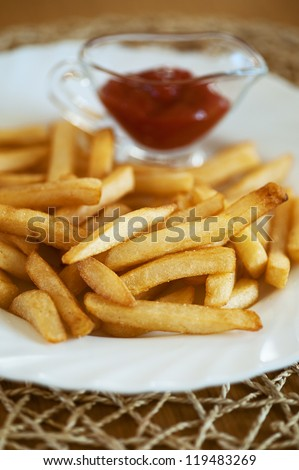 French fries and ketchup on large plate.